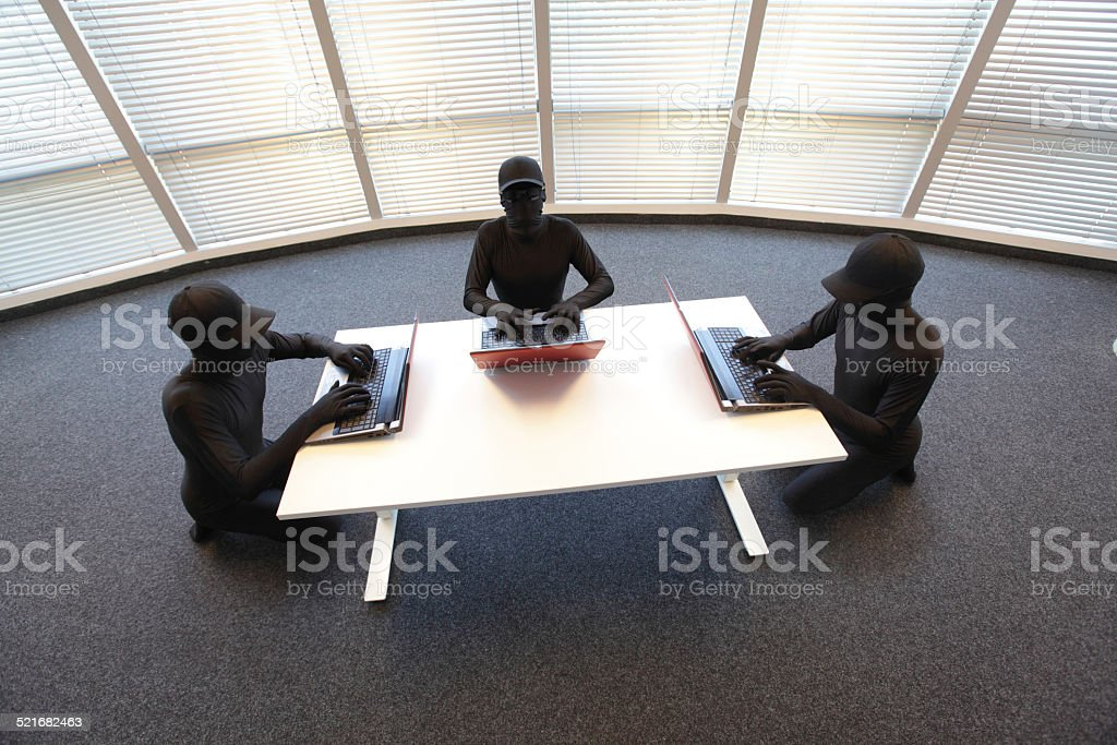 group of anonyous hackers working with computers in office stock photo