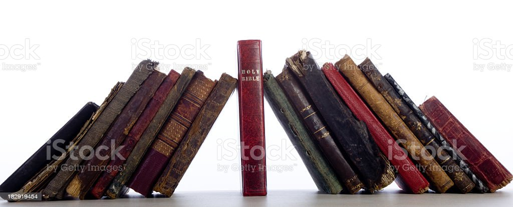 Group Of Antique Old Books Leaning On Bible As Keystone stock photo
