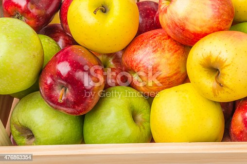 Group of apples in a wooden traditional box. Colorful composition of fruit.
