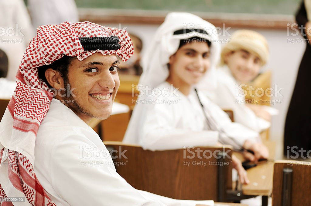 Group of Arabic students with eastern traditional clothes in classroom. stock photo