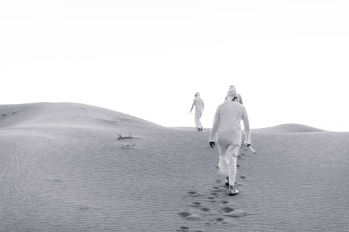 Black and White image of Arabs climbing the dunes of Arabia