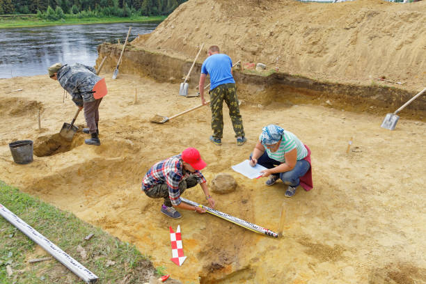 A group of archaeologists unearths an ancient burial.Sketch and entering the coordinates of the findings in the report of the expedition stock photo