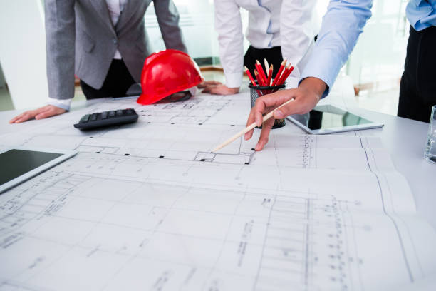 Group of architects and engineers discussing construction plans around a table stock photo