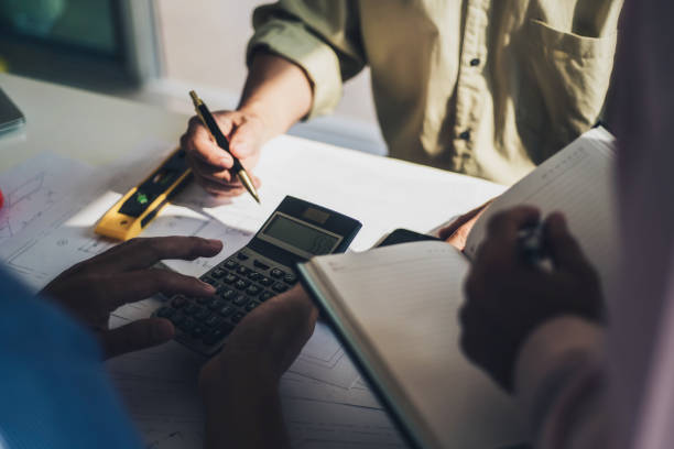 Group of architects discussing and useing calculator about calculate the cost with  for working building plan design project in office. Construction and structure concept. stock photo