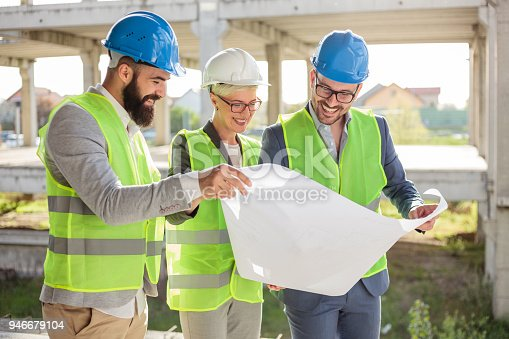 681242254 istock photo Group of architects or business partners discussing floor plans on a construction site 946679104