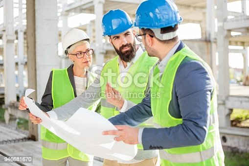 681242254 istock photo Group of architects or business partners having meeting on a construction site 946681670