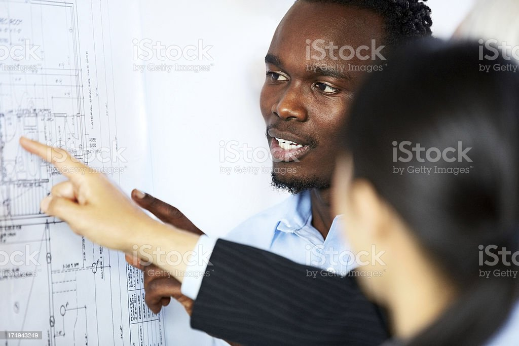Group of architects reviewing the building plan royalty-free stock photo