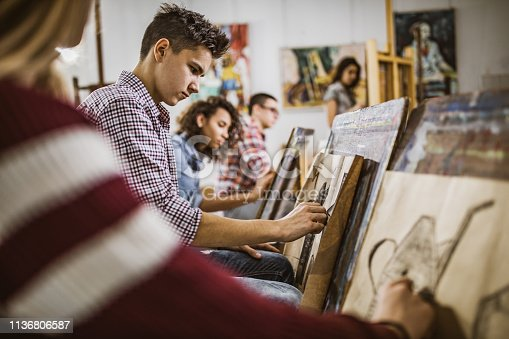Group of students drawing their paintings on a class at art studio. Focus is on male student.