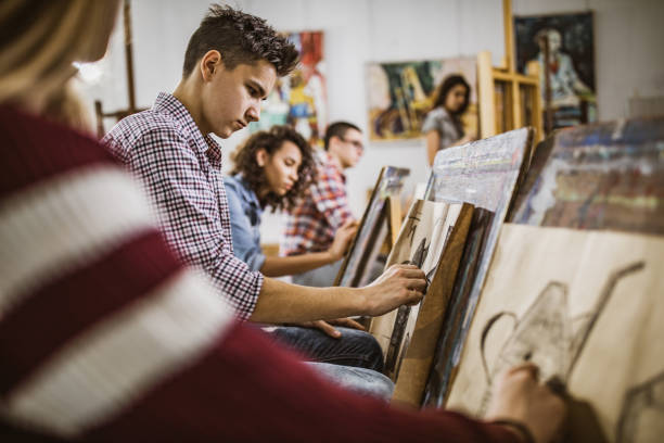 Group of art students drawing paintings at art studio. Group of students drawing their paintings on a class at art studio. Focus is on male student. artistry stock pictures, royalty-free photos & images