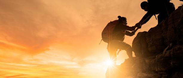 아시아 하이킹 그룹은 햇빛이 들어오는 산에서 서로 실루엣을 돕습니다. - 등산 뉴스 사진 이미지