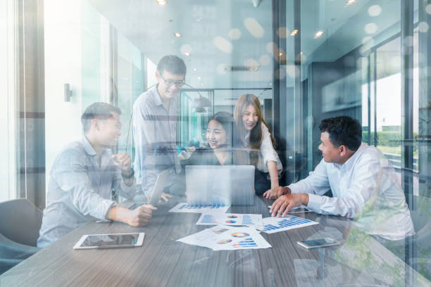 Group Of Asian and Multiethnic Business people with casual suit working and brainstorming together with technology computer in the modern Office, eople business group and entrepreneurship concept. stock photo