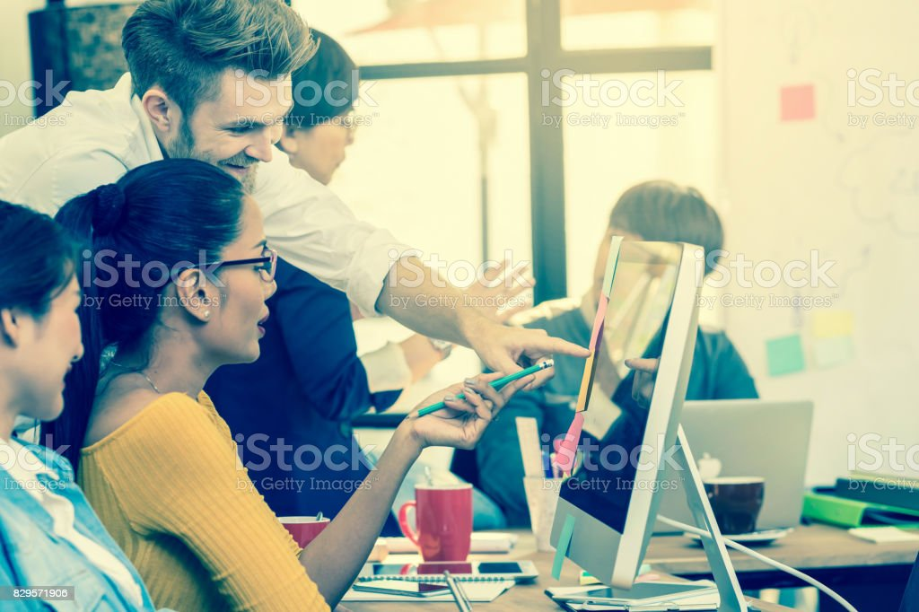 Group Of Asian and Multiethnic Business people with casual suit working in happy action with smart computer in the modern Office, people business group concept stock photo
