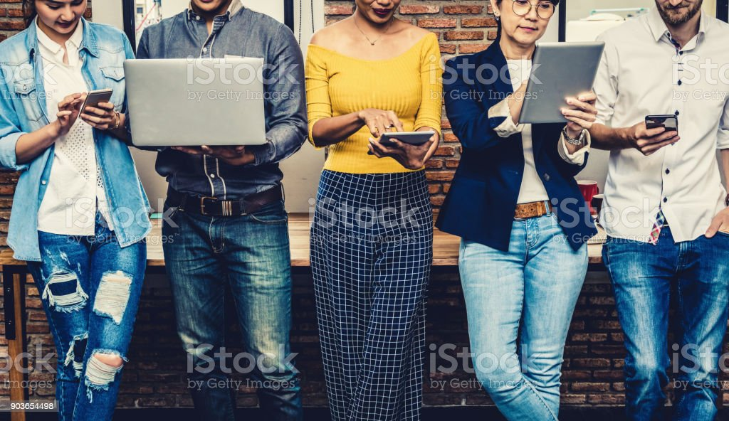 Group Of Asian and Multiethnic Business people with casual suit using the technology mobile, tablet, laptop and computer for working or social network in modern Office,people business group concept stock photo