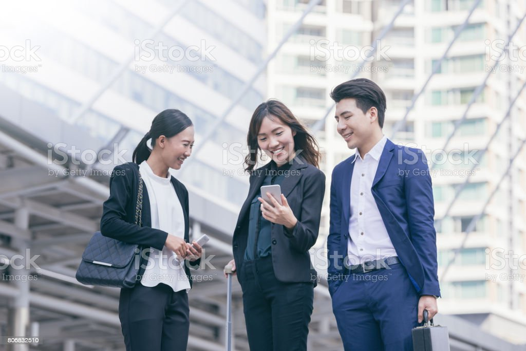 Group of Asian business colleagues using mobile phone's outside the office. stock photo