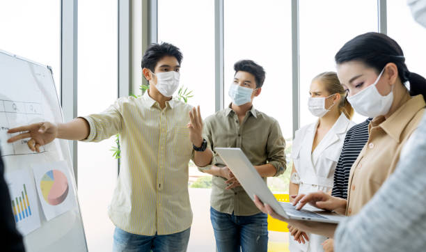 group of asian business people meeting and working in office and wear mask for protect  prevent infection corona virus covid 19. - businessman covid mask foto e immagini stock
