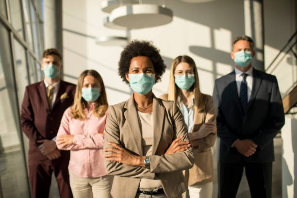Group of asian business people standing in office and wear mask for protect prevent infection by corona virus stock photo