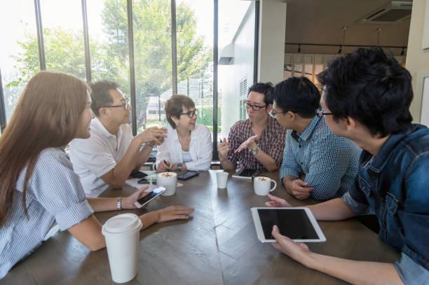 近代的なオフィスやコーヒー ショップ、人々 のグループ ショットの概念で会合し、カジュアルなスーツとアジアのビジネス人々 のグループ - 談笑する ストックフォトと画像