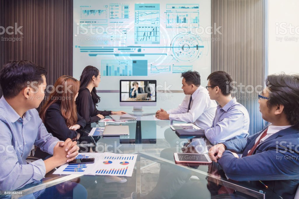 Group of asian Business team having video conference with their manager via monitor display in the modern conference room, Business people meeting concept stock photo