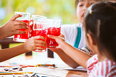 Group of asian children clinking glasses of fresh red juice water with ice and drinking together after finish their homework in the summer time