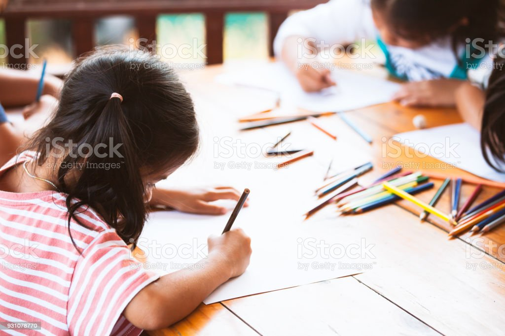 Group of asian children drawing and painting with crayon together...