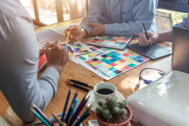 Group of Asian designers brainstorming working together with colleagues and color swatches in co-working workplace. stock photo