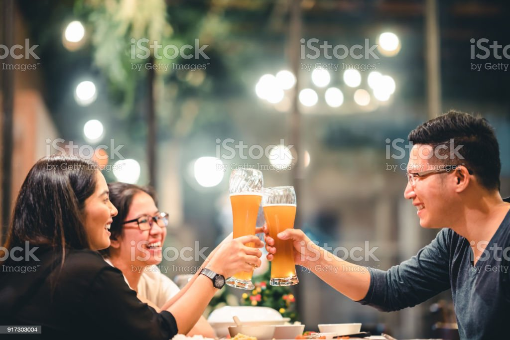Group of Asian friends or coworkers cheering with beer, celebrating together at restaurant or night club. Young people toasting at party event after work. Success or friendship concept. Focus on glass stock photo