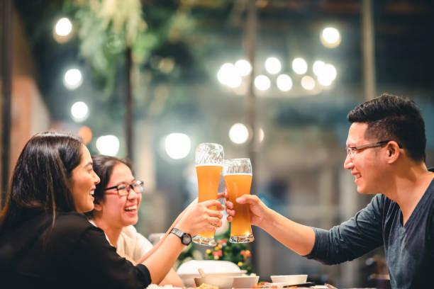 アジアの友人や同僚とビール、応援レストランや夜のクラブで一緒に祝うのグループ。若い人たちは、仕事の後のパーティー イベントで乾杯します。成功や友情の概念。ガラスに焦点を当てる ストックフォト