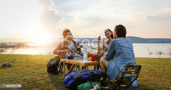 A group of Asian friends tourist drinking and playing guitar together with happiness in Summer while having camping near lake at sunset