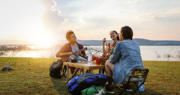 일몰 호수 근처에서 캠핑을하면서 아시아 친구 관광객 관광객이 여름에 행복과 함께 기타를 마시고 연주하는 그룹 - 야외활동 추구 뉴스 사진 이미지