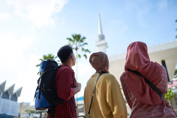 A group of Asian Muslim tourists enjoying the view of city mosque Asian female travellers in hijab and a man in front of a National Mosque in Kuala Lumpur touring stock pictures, royalty-free photos & images