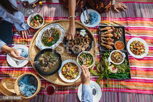 Group of Asian people family enjoy celebrating Thai food dinner while sitting on mat at home, Northeast thailand (Issan) healthy traditional Thai foods concept, Top view
