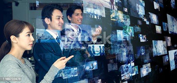 istock Group of asian people looking hologram screens. Streaming video. Social media. 1169722473