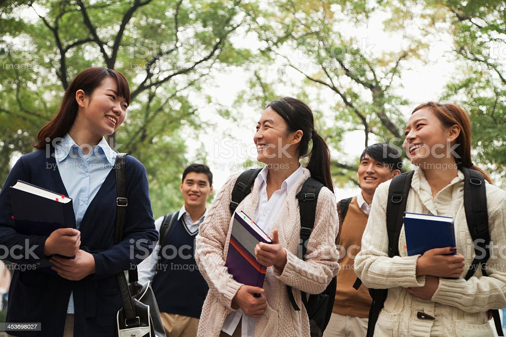 Group of Asian university students on campus with books stock photo