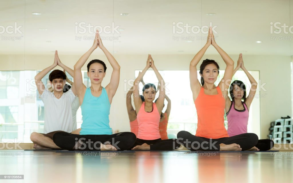 Group of asian women and man practicing yoga, fitness stretching flexibility pose, working out, healthy lifestyle, wellness, well being stock photo