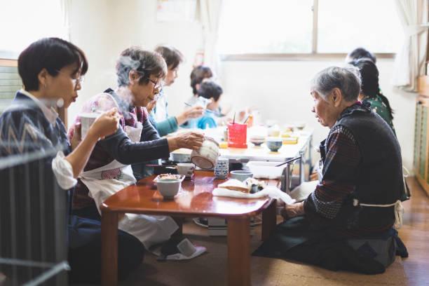 Grupo de mulheres asiáticas que têm o almoço ao trabalhar no estúdio - foto de acervo