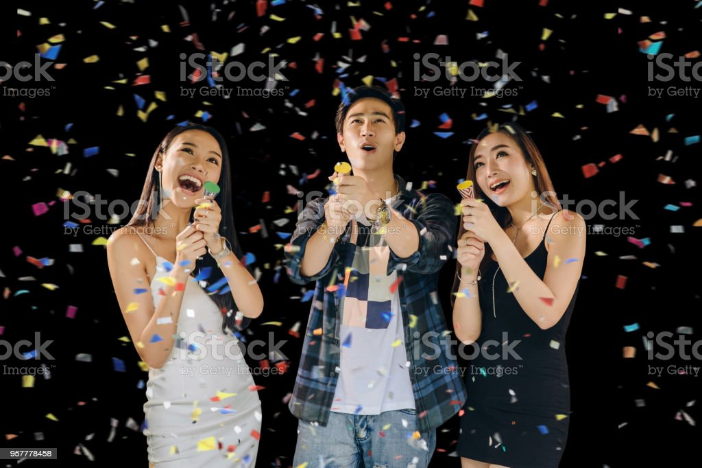 Group of asian young people having fun and enjoy with colorful confetti  in Christmas New Year.funny concept stock photo