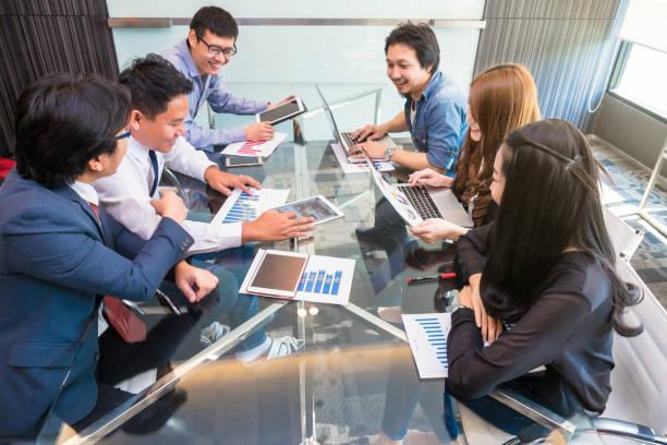 AsianBusiness グループ内の人カジュアル スーツ、近代的なオフィス、人々 ビジネス グループ コンセプトに幸福アクションとの出会い ストックフォト