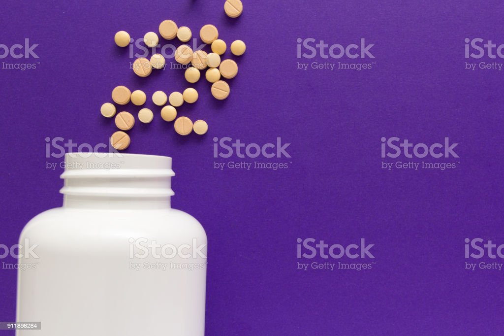 Group of assorted beige tablets. Capsules spilling out of white bottle. stock photo