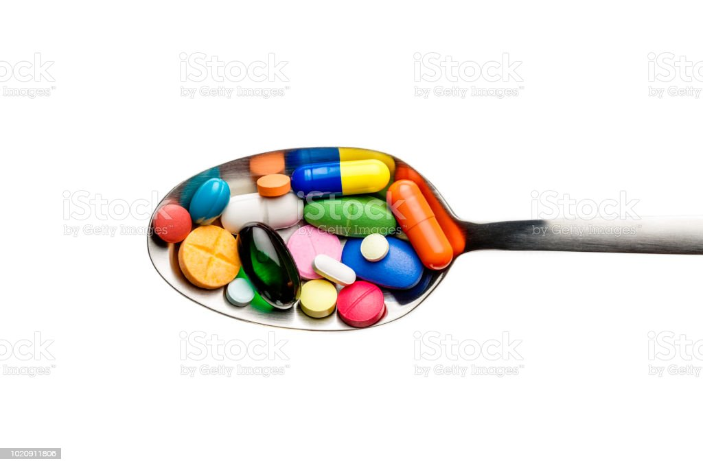 Group of assorted capsules and pills into a spoon on isolated white background stock photo
