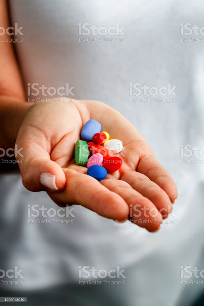 Group of assorted capsules and pills on young woman hands stock photo