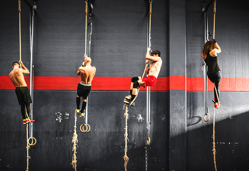 istock group of athlete climbing the rope on a gym 510793424
