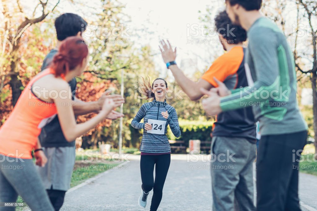 Group of athletes cheering a teammate at sports event stock photo