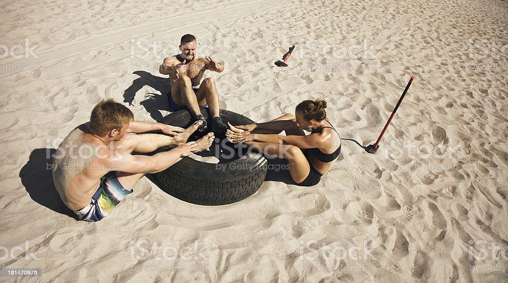 Group of athletes doing gym exercise routine on beach royalty-free stock photo