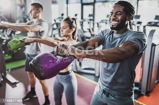 Happy black athlete and his friends having sports training with kettle bells in a gym.