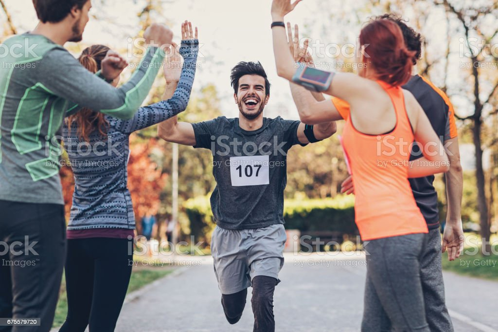 Group of athletes greeting the winner at the finsh line stock photo