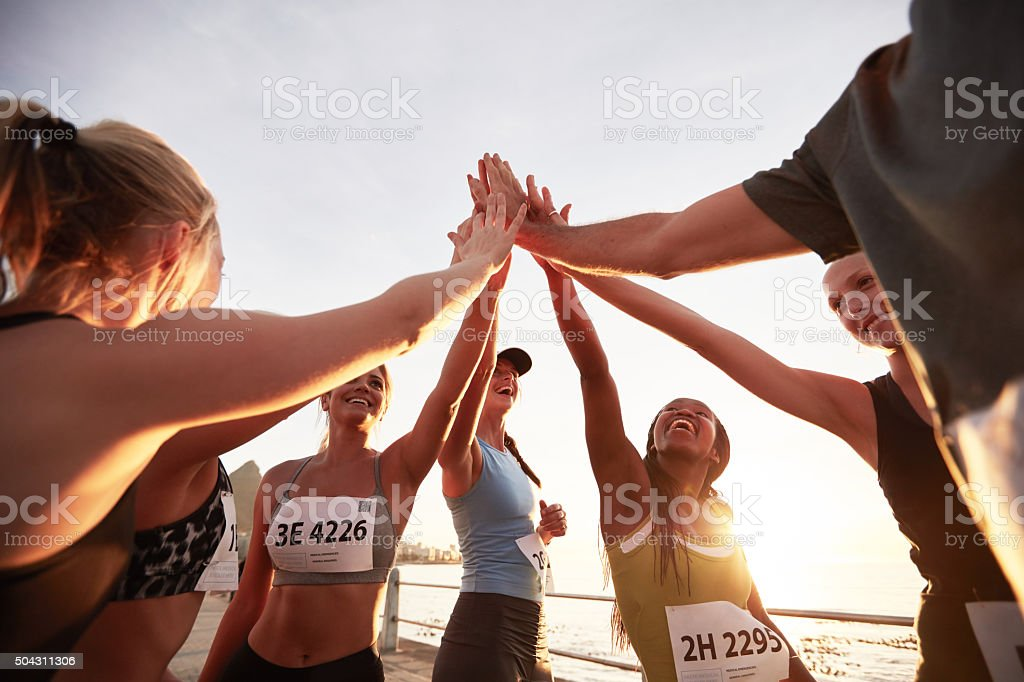 Group of athletes high fiving after race stock photo
