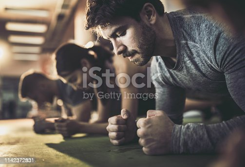 Sweaty athletic man making an effort while being in plank position with his friends in a gym.