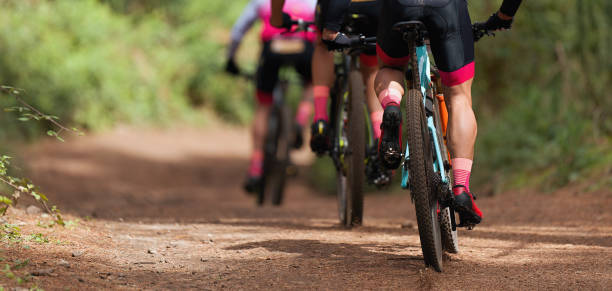 Group of athletes mountain biking on forest trail Group of athletes mountain biking on forest trail, mountain bike race mountain biking stock pictures, royalty-free photos & images