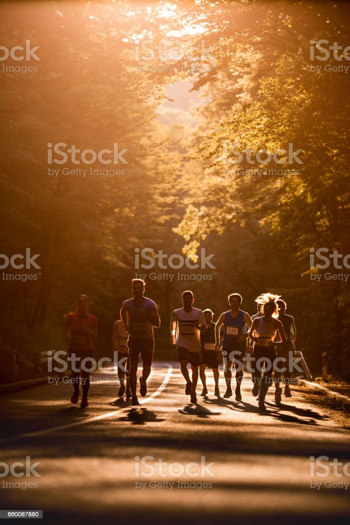 Group of athletes running a marathon in nature at sunset. stock photo