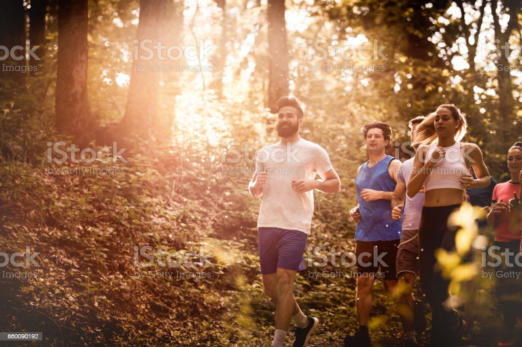 Group of athletes running a marathon race through the forest. stock photo